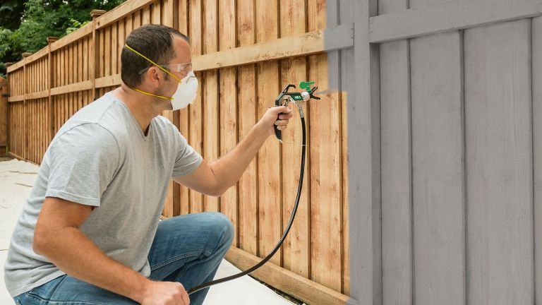 best paint sprayer: Man spraying fence with paint sprayer