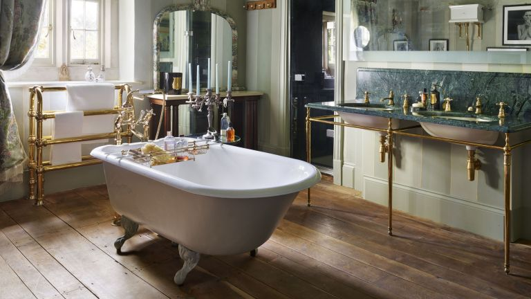 A master bathroom with central freestanding tub, traditional brass fittings and a green marble double vanity