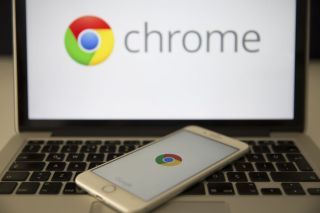 Google Chrome Logo on a laptop with a smartphone resting on its its keys also displaying the Chrome logo