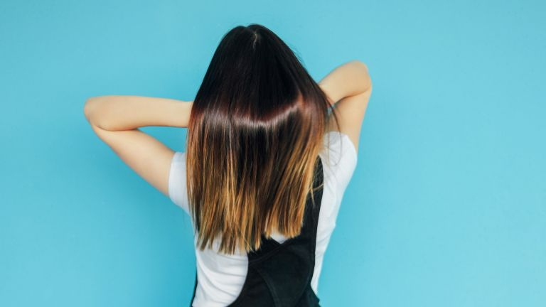 Rear View Of Woman With Long Dyed Hair Standing Against Blue Background - stock photo Photo taken in Yekaterinburg, Russia