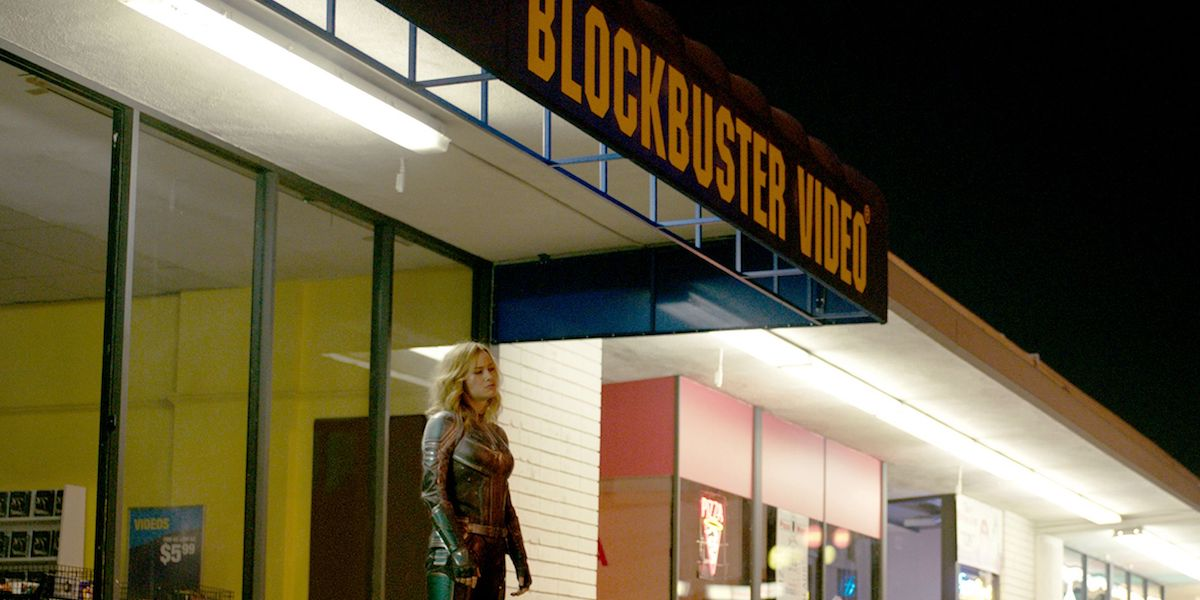 Brie Larson as Captain Marvel in front of Blockbuster Video in the 1990s