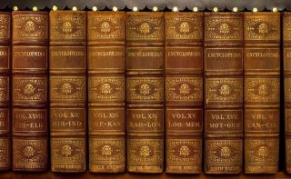 Retro-looking encyclopedias on a book shelf.
