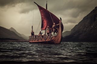 Group of vikings are floating on the sea on Drakkar with mountains in the background.