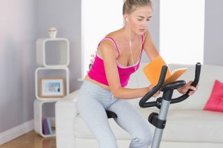 A woman reads a book while riding a stationary bike.