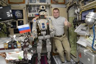 Russia's Skybot F-850 humanoid robot holds a Russian flag with cosmonaut Alexey Ovchinin for a photo in the Zvezda service module of the International Space Station in this photo released Sept.