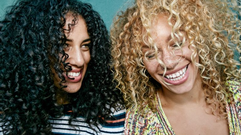 Two women with curly hair laughing