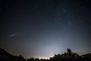 A Perseid Meteor flashes across the night sky above Corfe Castle on August 12, 2016 in Corfe Castle, United Kingdom.