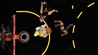 Alex Caruso #4 of the Los Angeles Lakers slam dunks the ball past Devin Booker #1 and Cameron Payne #15 of the Phoenix Suns during the second half of Game Two of the Western Conference first-round playoff series at Phoenix Suns Arena on May 25, 2021 in Phoenix, Arizona.