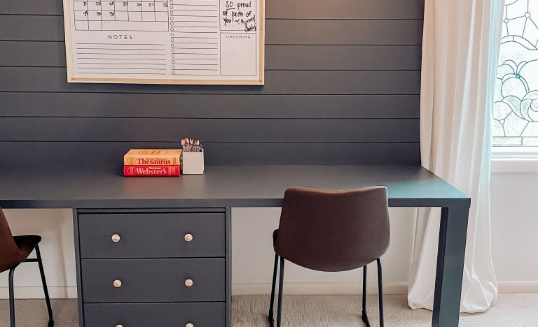 Teal blue built-in desk with black chairs and books on top