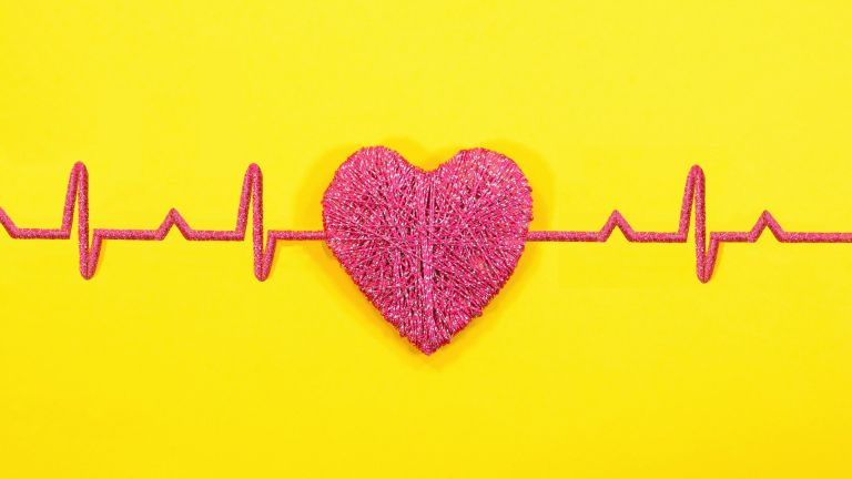 Red heart shape with heart beat readings on yellow background.