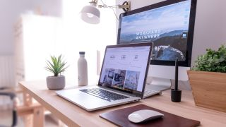 MacBook and iMac on desk in home office