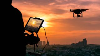 Best camera drones: Silhouette of Man using drone to monitor the city at the evening, city sunset background.