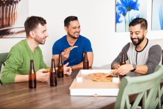 Three guys hang out together, eating pizza
