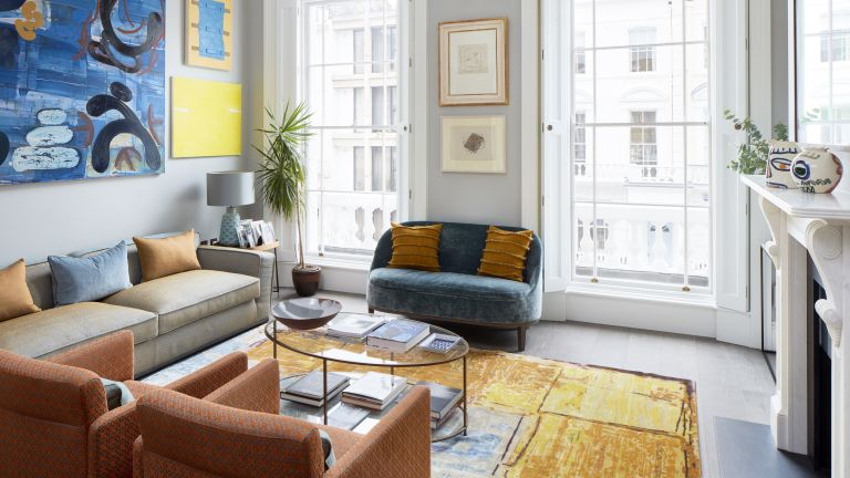 A drawing room with orange armchairs, a yellow and blue rug and contemporary pendant chandelier