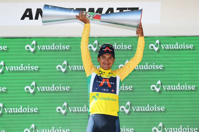 Richard Carapaz lifts the Tour de Suisse trophy aloft while wearing the leaders yellow jersey