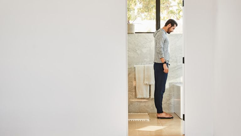 Fitbit Aria Air review: men looking at bathroom scale