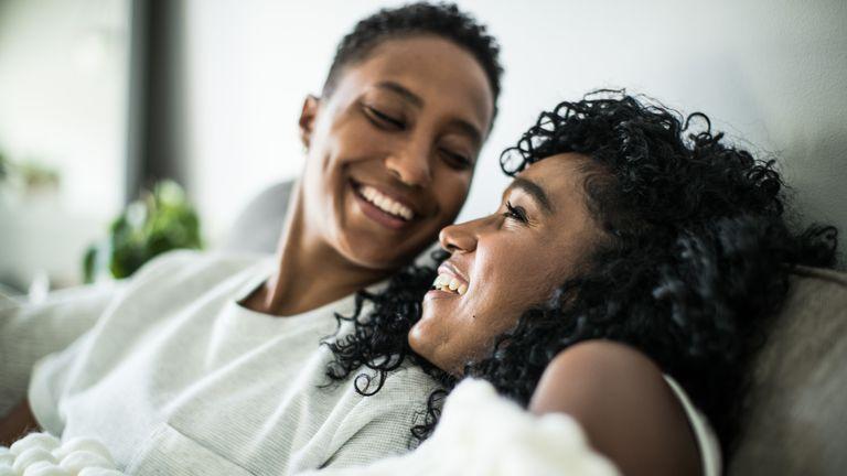 female couple on sofa laughing