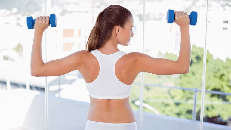 Woman doing a 30-day arms workout with dumbbells