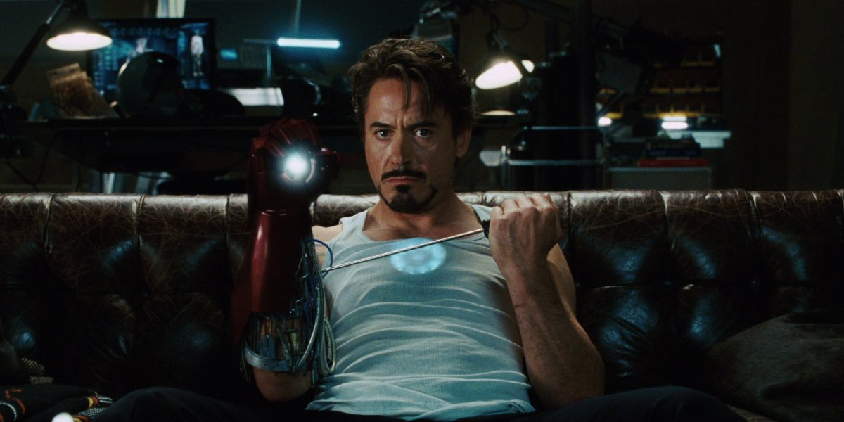 Robert Downey Jr sits on the couch testing a Repulsor glove in Iron Man.