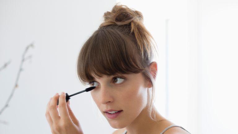 Close-up of a woman applying mascara - stock photo