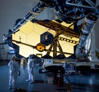 The reflections of two spacecraft technicians are captured in the gold-plated mirrors of NASA's James Webb Space Telescope (JWST). Currently under construction at Northrop Grumman's Los Angeles facility, JWST is scheduled to launch in 2021. According to one new study, Webb could help scientists to detect and study atmospheres in the TRAPPIST-1 planetary system.