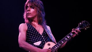 A photograph of Randy Rhoads on stage playing a Gibson Les Paul guitar