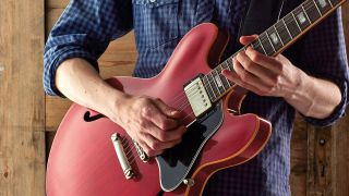 Man playing hollowbody electric guitar