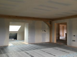 Underfloor heating being installed in a oak frame home