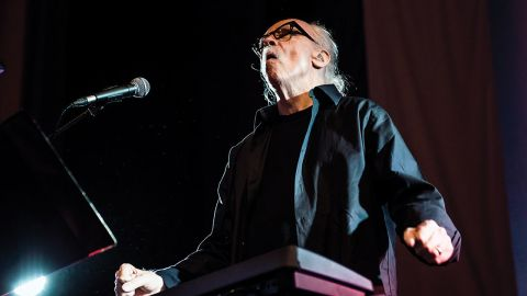 A photograph of John Carpenter on stage