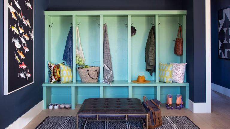 mudroom with blue storage unit with stalls, foot stool and storage shelf - Andrea Schumacher