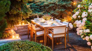 Backyard lighting ideas: image of illuminated dinner setting with greenery