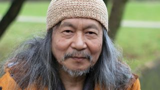 Damo Suzuki modern portrait wearing a crochet hat and orange anorak