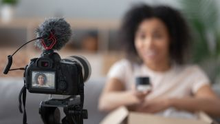 Best cameras for vlogging — a women sitting in front of a camera