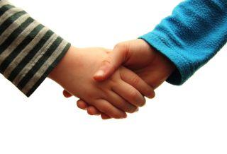 Two kids shake hands.