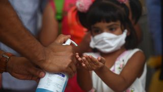 A child in Bangladesh receives a squirt of hand sanitizer to ward off COVID-19 in a March 2020 photo. There's been a sharp uptick in chemical burns from sanitizer to children's eyes since the start of the pandemic, largely due to public dispensers.