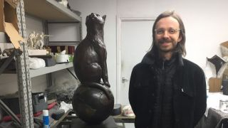 Matthew Serge Guy, who created a fundraising campaign to build a memorial for the first cat in space, poses with the completed statue of Félicette.