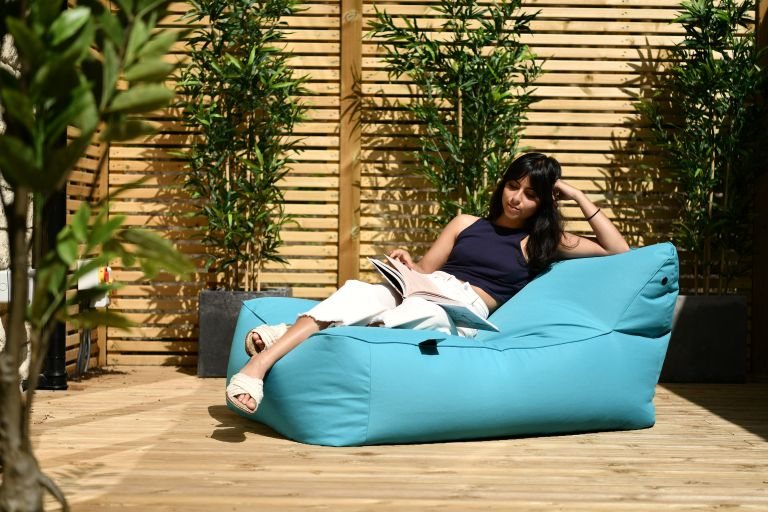 outdoor bean bags: blue bean bag lounger in a modern garden with a women lying on it