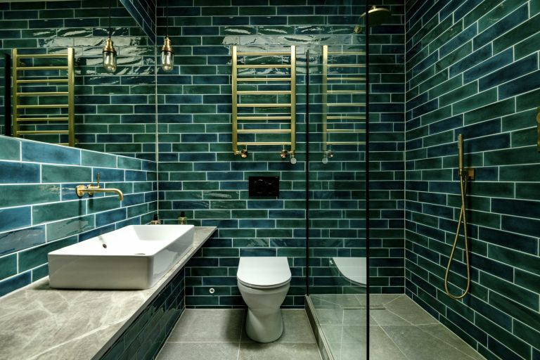 An example of green bathroom ideas showing a bathroom with green wall tiles and brass fixtures and fittings with a glass shower door