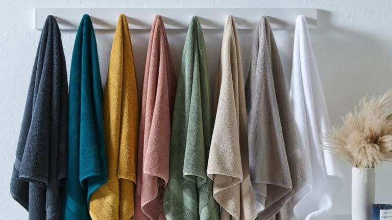 Furn The Linen Yard Loft Combed Cotton 7-piece Towels in each colour hanging on hooks on wall