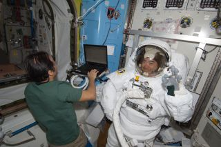 Japanese astronaut Akihiko Hoshide of JAXA waves while testing his spacesuit inside the International Space Station ahead of an Aug. 30, 2012 spacewalk with crewmate Sunita Williams of NASA.