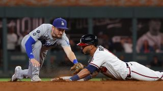 Eddie Rosario #8 of the Atlanta Braves slides safely into second base ahead of the tag of Trea Turner #6 of the Los Angeles Dodgers in the eighth inning of Game Two of the National League Championship Series at Truist Park on Oct. 17, 2021 in Atlanta, Georgia.