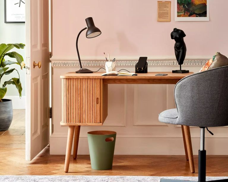 John Lewis & Partners Grayson Desk with fluted cupboard and angled legs infront of pink wall with grey desk chair and green bin underneath
