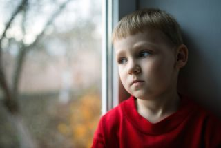 A young boy looks out a window, looking very sad.
