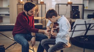 Man shows boy how to play the acoustic guitar