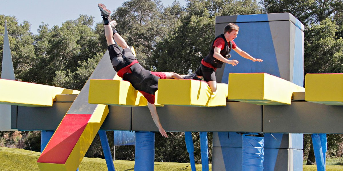 Competitors stumble on an obstacle on Wipeout