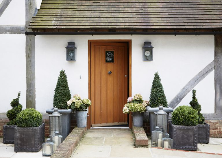 Front garden with stone paving leading to wooden door with topiary plants