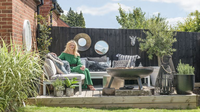 Woman sitting on outdoor corner sofa with firepit and dark fence