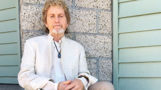 Jon Anderson leaning against a wall