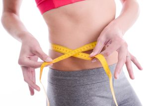A woman measures her waistline