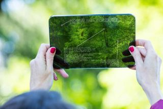Hands of a woman using augmented reality on a high tech transparent digital tablet